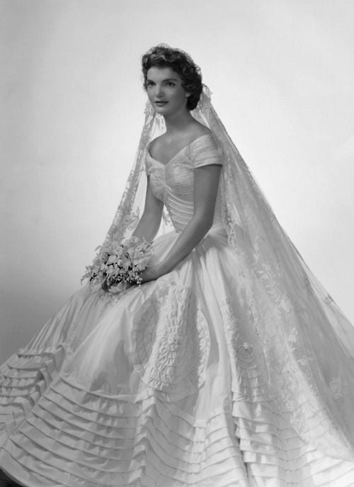 Jacqueline Bouvier The future first lady (and fashion icon) wore a voluminous ivory silk taffeta gown by the designer Ann Lowe when she married John F. Kennedy in 1953. A portrait neckline and wide, embellished skirt emphasized Jackie's small waist, and an heirloom lace veil, which originally belonged to her grandmother, completed the super-romantic ensemble., abiti da sposa più belli di sempre, best weeding dress of ever, eleonora carisi sposa, eleonora carisi matrimonio, theladycracy.it, elisa bellino, fashion blog 2016, fashion blogger famose 2016, fashion blogger italia 2016, fashion blogger italiane, fashion bloggers 2016,